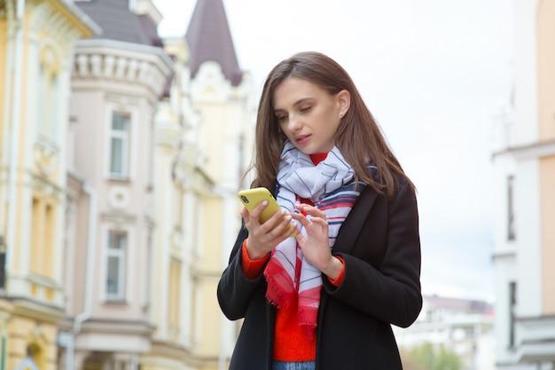 Jonge vrouw met een mobiele telefoon op een stad