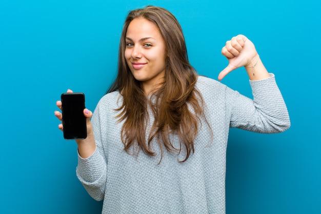 Jonge vrouw met een mobiele telefoon tegen blauwe achtergrond