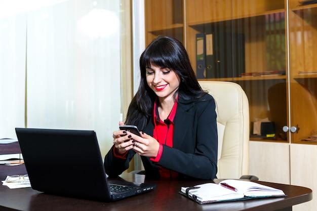 Jonge vrouw met een mobiele telefoon zit aan de balie in het kantoor
