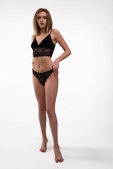 Jonge vrouw met een mooi figuur in zwart kanten ondergoed