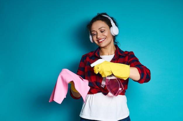 Jonge vrouw met een mooie brede glimlach die een wasmiddelnevel op een doek, schoonmakend concept toepast dat op blauw wordt geschoten