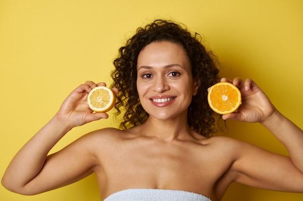 Jonge vrouw met een mooie glimlach die de helften van sinaasappel en citroen dichtbij haar gezicht houdt. concepten, gezond eten, huid- en lichaamsverzorging.