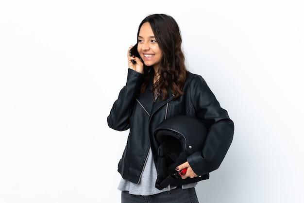 Jonge vrouw met een motorhelm over geïsoleerde witte koffie te houden om mee te nemen en een mobiel