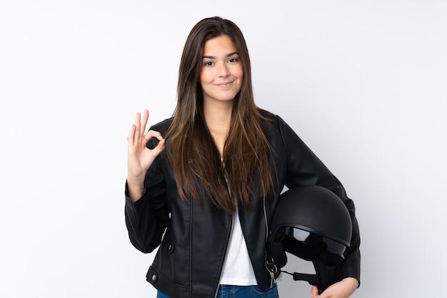 Jonge vrouw met een motorhelm over geïsoleerde witte muur die een ok teken met vingers toont
