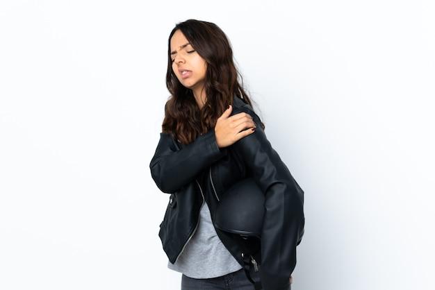 Jonge vrouw met een motorhelm over geïsoleerde witte muur die lijdt aan pijn in de schouder omdat ze zich heeft ingespannen