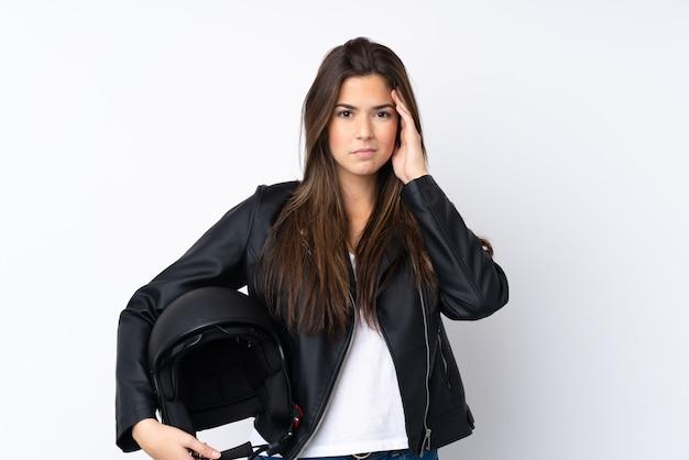 Jonge vrouw met een motorhelm over geïsoleerde witte muur ongelukkig en gefrustreerd met iets. negatieve gezichtsuitdrukking