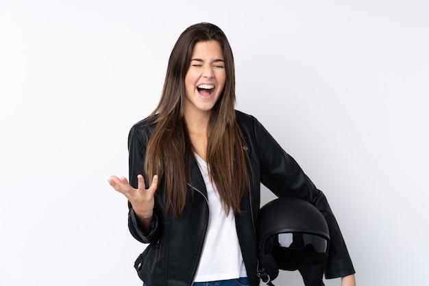 Jonge vrouw met een motorhelm over geïsoleerde witte muur ongelukkig en gefrustreerd met iets