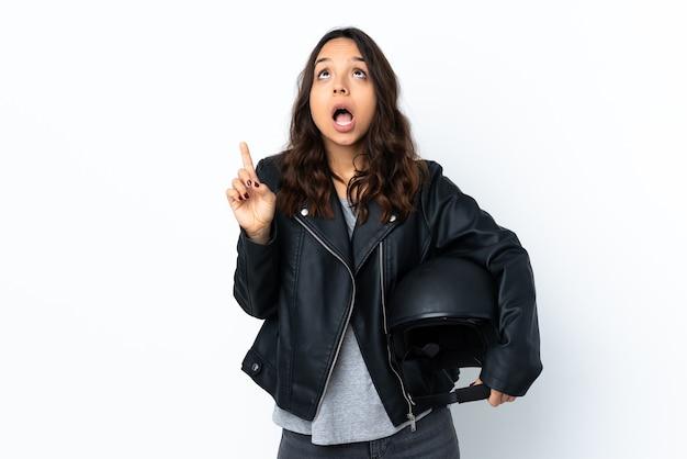 Jonge vrouw met een motorhelm over geïsoleerde witte muur verrast en benadrukt