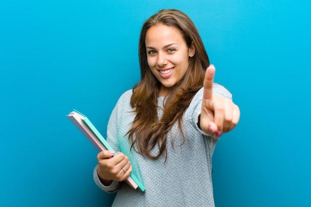 Jonge vrouw met een notitieboekje tegen blauwe achtergrond