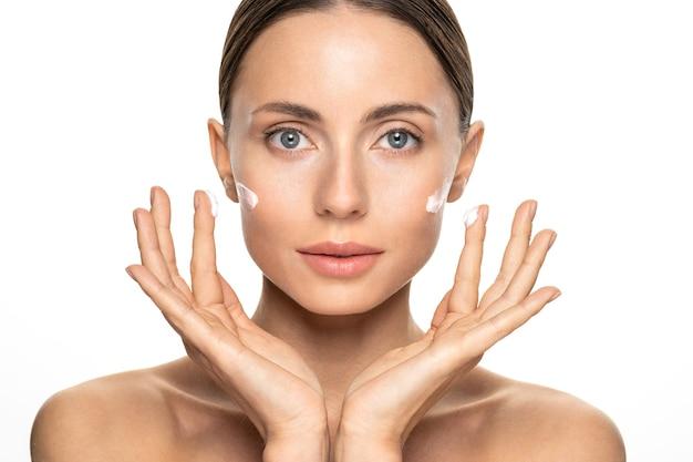 Jonge vrouw met een onberispelijke huid die voedende room op haar gezichtwang en vingers toepast