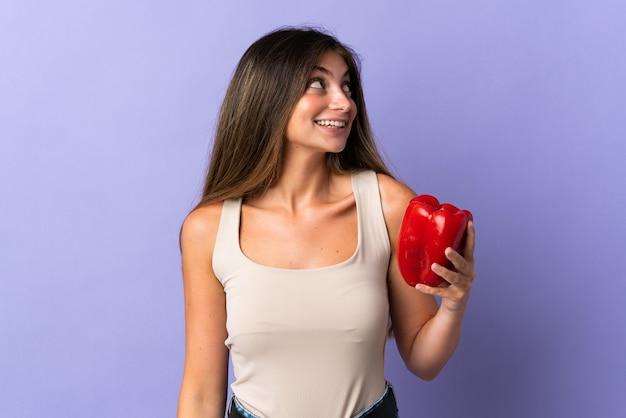 Jonge vrouw met een peper geïsoleerd op paars opzoeken tijdens het glimlachen