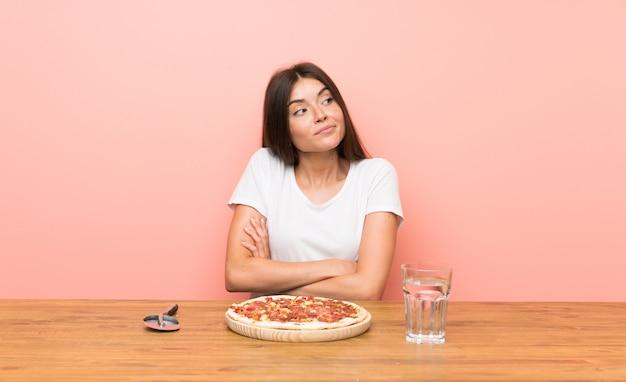 Jonge vrouw met een pizza die twijfel maakt terwijl het opheffen van de schouders