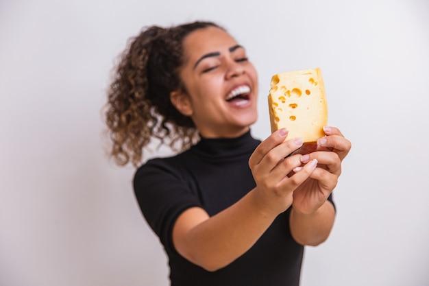 Jonge vrouw met een plakje kaas in haar hand. vrouw die parmezaanse kaas eet. focus op kaas