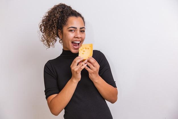 Jonge vrouw met een plakje kaas in haar hand. vrouw die parmezaanse kaas eet