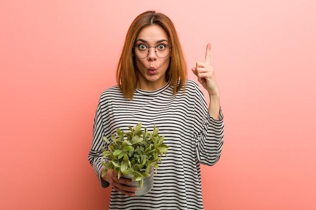 Jonge vrouw met een plant met een geweldig idee