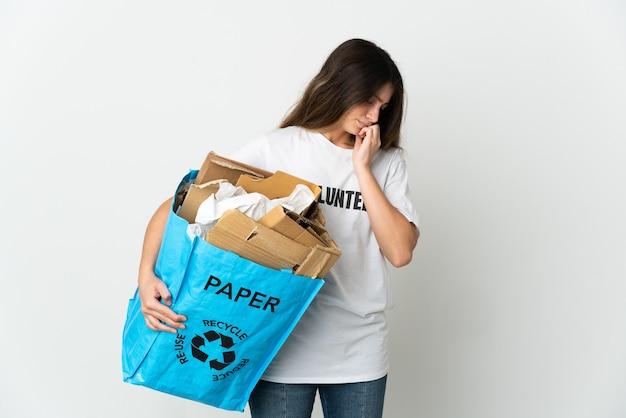 Jonge vrouw met een recycling zak vol papier om te recyclen op wit met twijfels