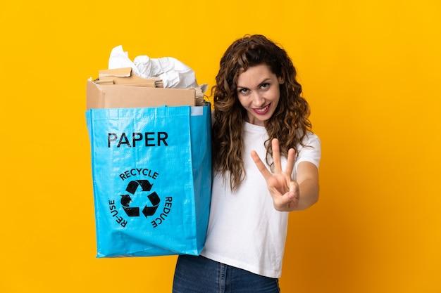 Jonge vrouw met een recyclingzak vol papier om te recyclen