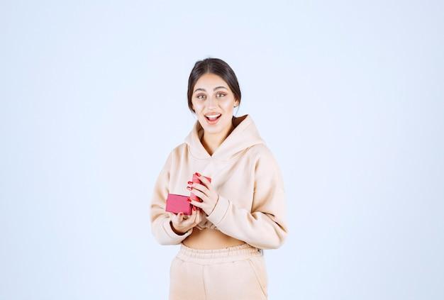 Jonge vrouw met een rode geschenkdoos ziet er blij en verrast uit