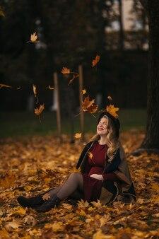 Jonge vrouw met een rode jurk en zwarte hoed zit op de grond onder de vallende gele bladeren op ...