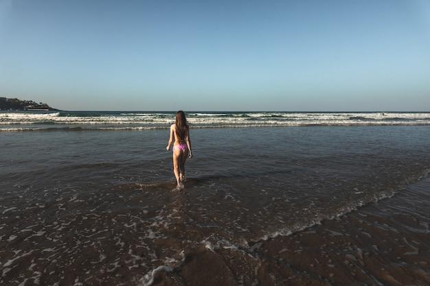 Jonge vrouw met een roze bikini die naar de zee gaat