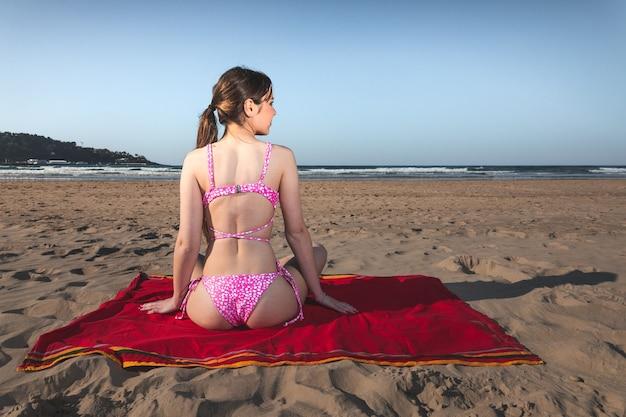 Jonge vrouw met een roze bikini op een rode handdoek op het strand