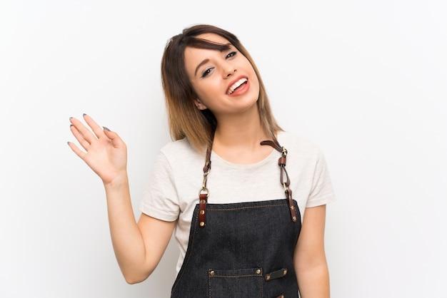 Jonge vrouw met een schort die met hand met gelukkige uitdrukking groeten