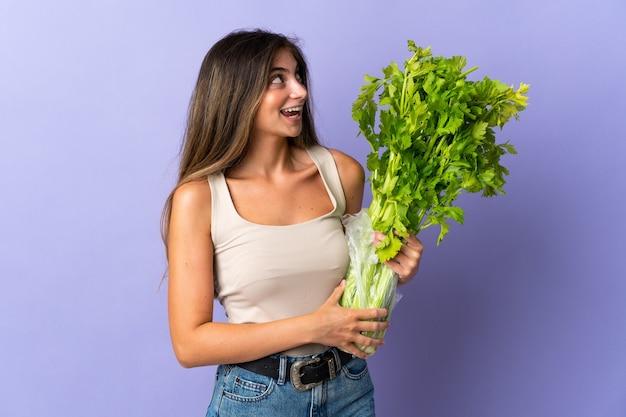 Jonge vrouw met een selderij geïsoleerd op paars opzoeken tijdens het glimlachen