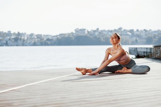 Jonge vrouw met een slank type lichaam doet oefeningen tegen meer