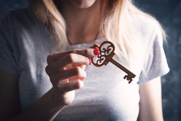 Jonge vrouw met een sleutel in haar hand op een grey