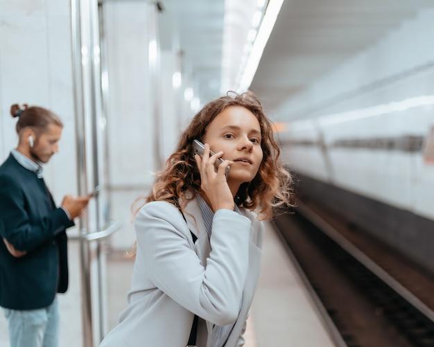 Jonge vrouw met een smartphone die op het metroperron staat