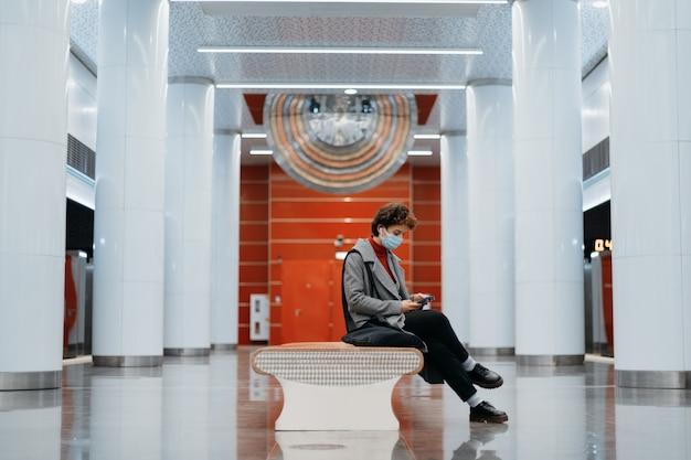 Jonge vrouw met een smartphone zittend op een bankje in de metro