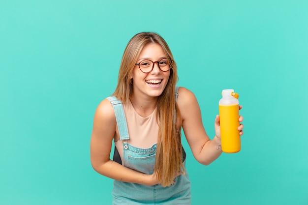 Jonge vrouw met een smoothy die hardop lacht om een hilarische grap