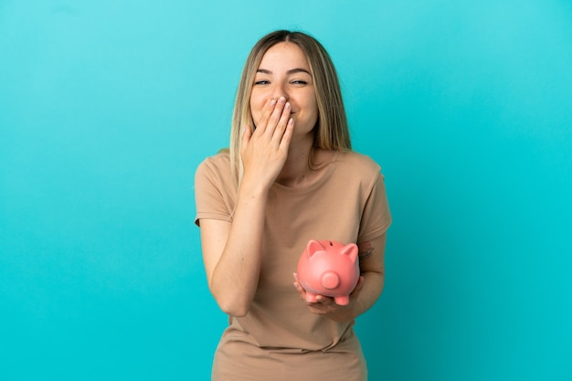 Jonge vrouw met een spaarpot over een geïsoleerde blauwe achtergrond, blij en glimlachend die de mond bedekt met de hand