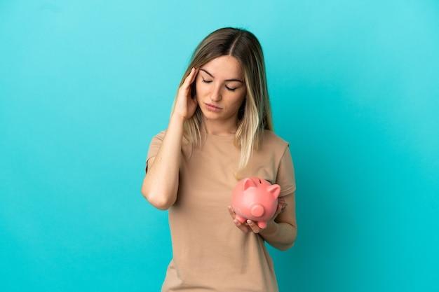 Jonge vrouw met een spaarpot over geïsoleerde blauwe achtergrond met hoofdpijn