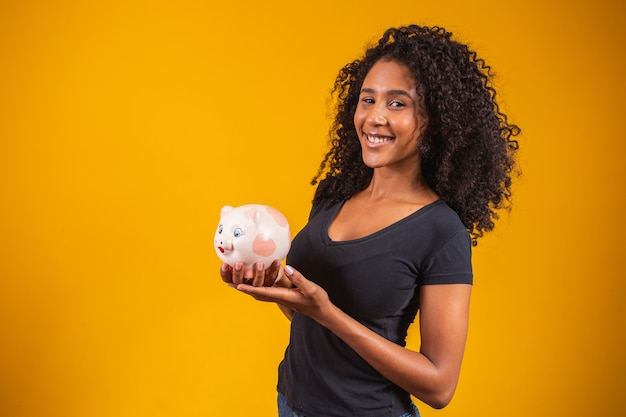 Jonge vrouw met een spaarvarken op een stevige achtergrond
