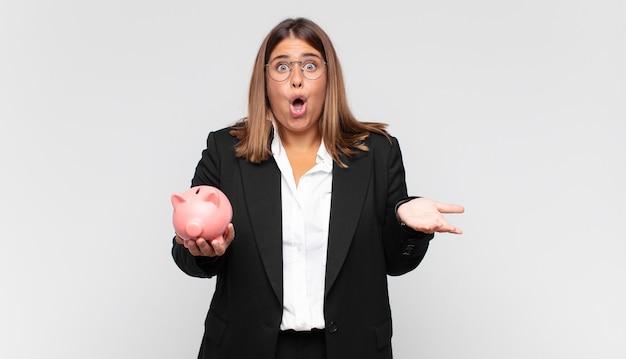 Jonge vrouw met een spaarvarken voelt zich extreem geschokt en verrast, angstig en in paniek, met een gestresste en geschokte blik