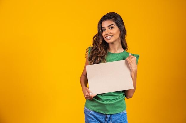Jonge vrouw met een spandoek met ruimte voor tekst.