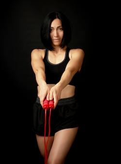 Jonge vrouw met een sport figuur in zwart uniform houdt een rood touw voor het springen