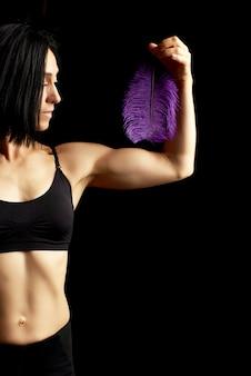 Jonge vrouw met een sportfiguur en spieren gekleed in zwarte kleding houdt een paarse veer in haar linkerhand