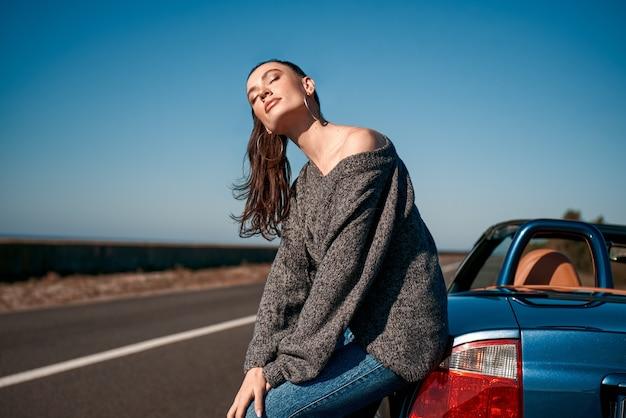 Jonge vrouw met een staart die buiten in de buurt van een auto zonder dak staat