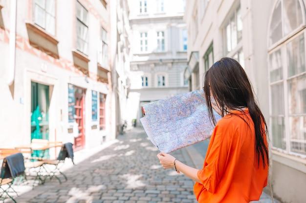 Jonge vrouw met een stadskaart in de stad.