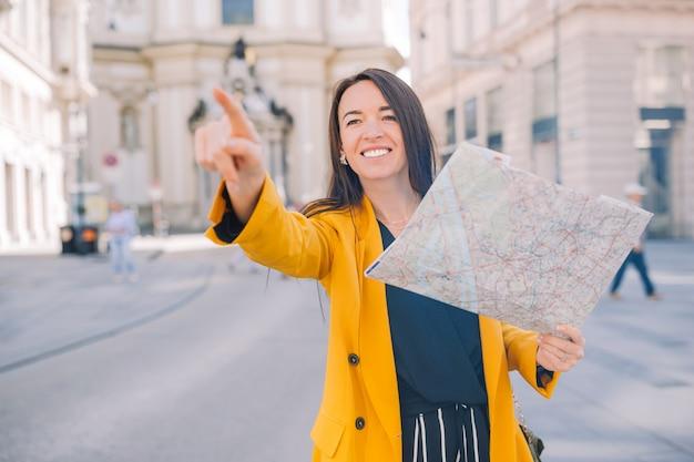 Jonge vrouw met een stadskaart in stad die op iets richt