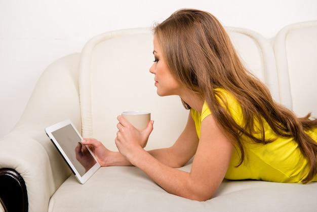 Jonge vrouw met een tablet die van de kopholding op de bank ligt