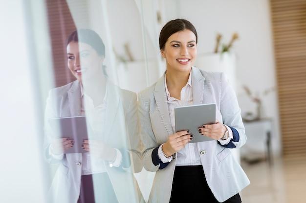 Jonge vrouw met een tablet in het kantoor