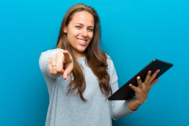 Jonge vrouw met een tablet tegen blauw