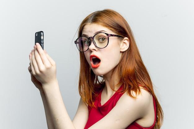Jonge vrouw met een telefoon in haar handen, lichte achtergrond