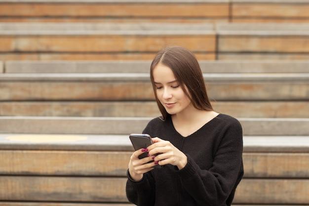 Jonge vrouw met een telefoon op straat op een bankje glimlacht