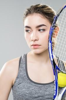 Jonge vrouw met een tennisracket over haar geïsoleerd gezicht. neutraal gezicht en zelfverzekerde uitstraling. close-up shot.