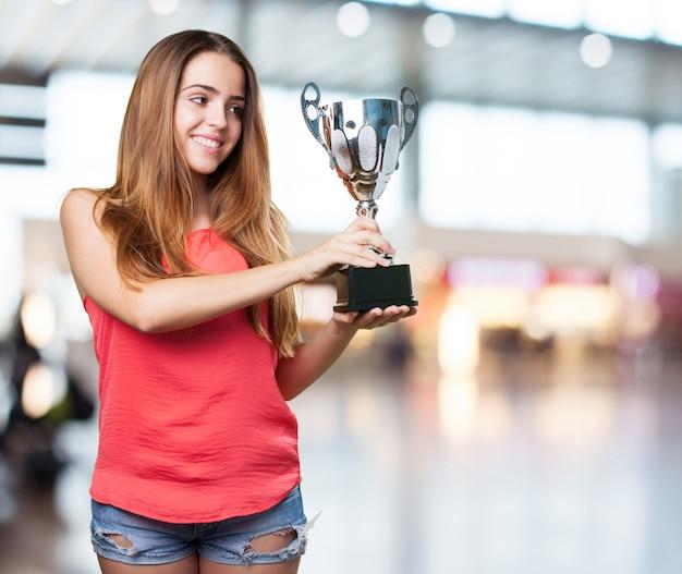 Jonge vrouw met een trofee op een witte achtergrond