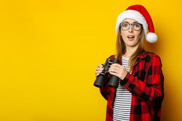 Jonge vrouw met een verbaasd gezicht en in een kerstmuts en een rood shirt in een kooi houdt een verrekijker vast